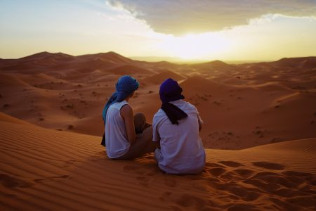 Two people sitting on sand dunes